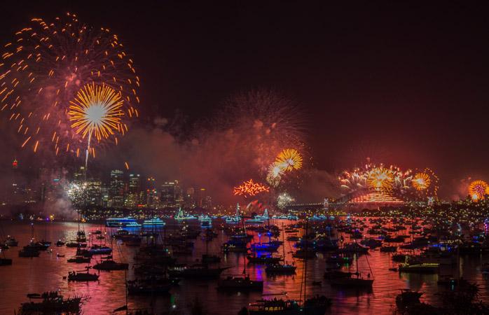 Fira in det nya året ombord på en av de många båtarna i Sydneys hamns färgsprakande ljusparad